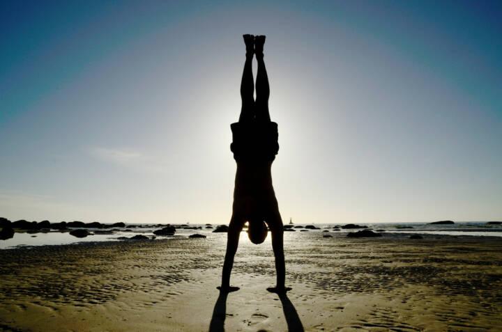 Kopfstehen, Kopf stehen, über Kopf, Hals über Kopf, Balance, Balanceakt, Ausgleich, ausgeglichen, http://www.shutterstock.com/de/pic-110665073/stock-photo-asian-man-acts-yoga-on-the-beach-turn-upside-down-and-standing-by-hands-silhouetted-against.html