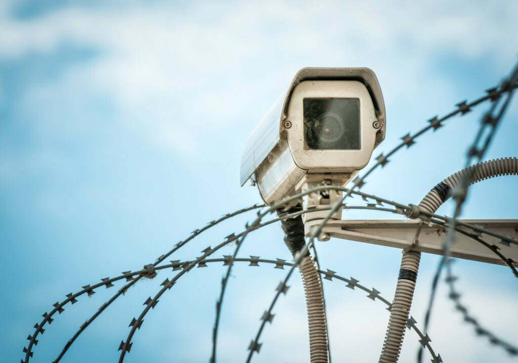 Überwachung, Kamera, Stacheldraht, sicher, gesichert, versperrt, Spionage, Sicherheit, eingesperrt, http://www.shutterstock.com/de/pic-132392237/stock-photo-close-up-view-of-security-camera-hanging-among-barbwire-in-prison-or-other-guarded-object-with-blue.html , © (www.shutterstock.com) (21.07.2014)