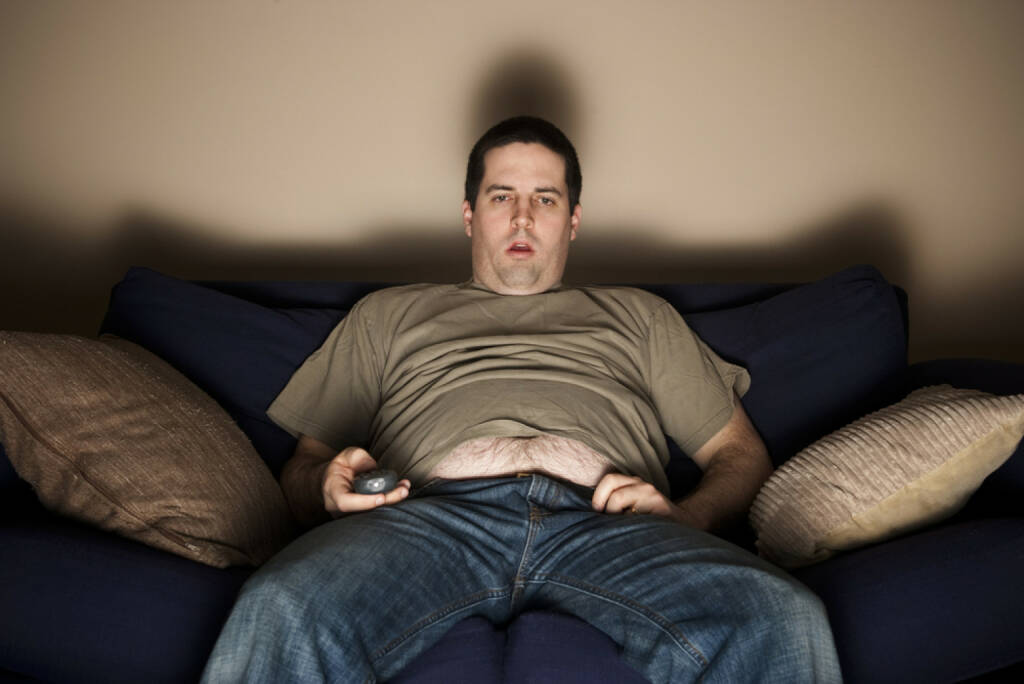couch potatoe, Sofa, Mann, http://www.shutterstock.com/de/pic-96088505/stock-photo-overweight-slob-watches-tv-with-belly-showing.html, © www.shutterstock.com (01.11.2014)
