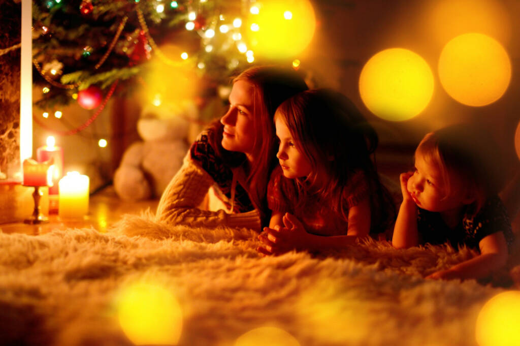 Weihnachten, Bescherung, Heiliger Abend, http://www.shutterstock.com/de/pic-215615716/stock-photo-young-mother-and-her-two-little-daughters-sitting-by-a-fireplace-in-a-cozy-dark-living-room-on.html, © www.shutterstock.com (05.11.2014)
