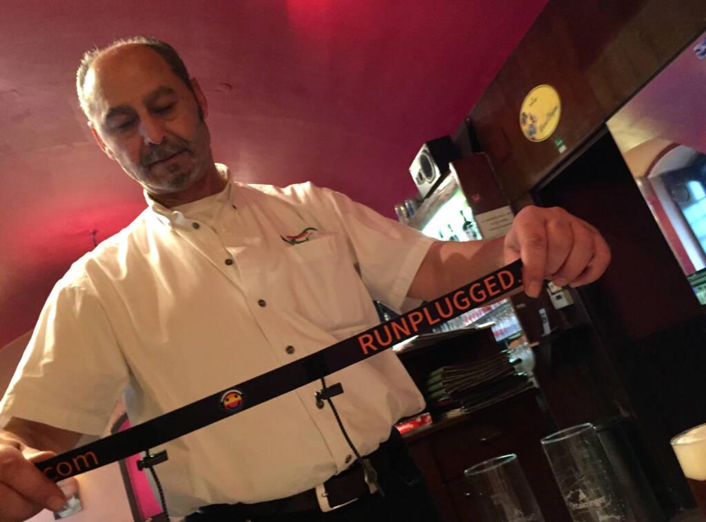 Der Besitzer der Pizzeria Valentino, der eine Runplugged Pizza gestalten wird, mit dem neuen Runplugged Startnummernband (11.12.2014)