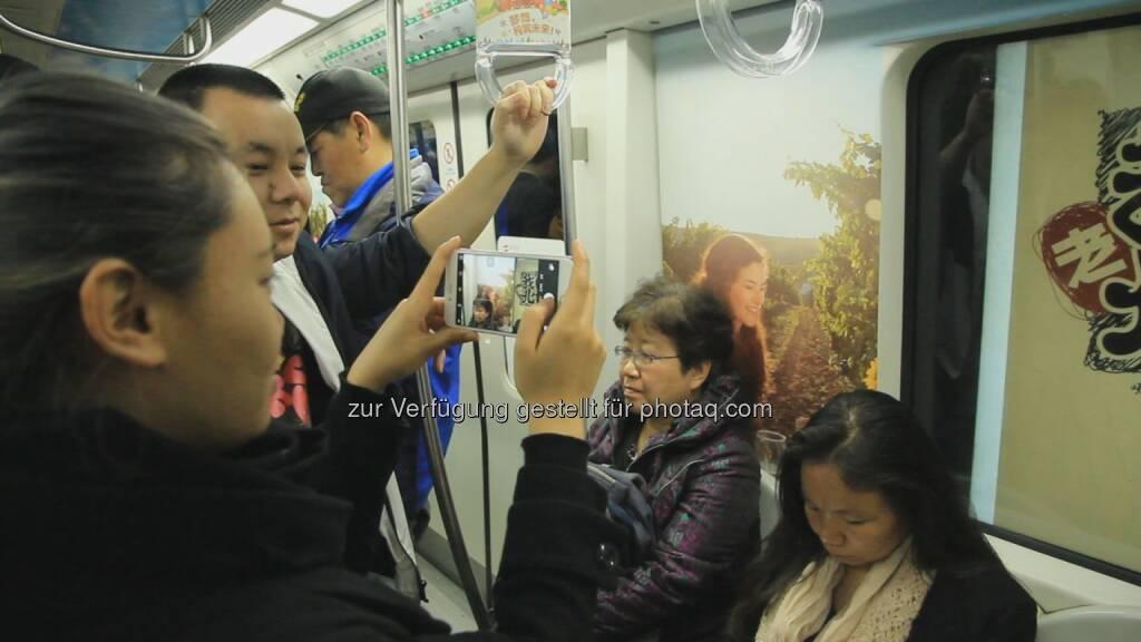 Passagiere in der Österreich-gebrandeten U-Bahn in Peking : Österreich-Rundreise mit der U-Bahn : Von 29. März bis 28. April 2016 werden in Peking zwei U-Bahn-Züge der Linie 10 - an der gesamten Innenseite mit österreichischen Motiven beklebt - unterwegs sein : Fotocredit: Österreich Werbung, © Aussender (30.03.2016)