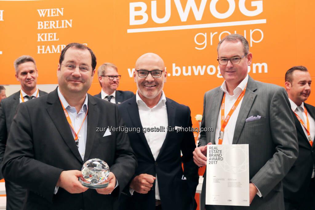 """Im Rahmen der Expo Real – der internationalen Fachmesse für Immobilien und Investitionen in München – wurden die Top-Player der Immobilienbranche ausgezeichnet. Zum dritten Mal in Folge konnte sich die Buwog Group den ersten Platz in der Kategorie """"Top 100 Residential Österreich"""" sichern. Hierbei erreichte die Marke im diesjährigen Ranking mit einem Brandvalue von 86,48 Prozent den Bestwert aller untersuchten Unternehmen. Buwog-CEO Daniel Riedl (links) und Buwog-COO Herwig Teufelsdorfer (rechts) gemeinsam mit Harald Steiner, Herausgeber des Real Estate Brand Books; Fotocredit: Buwog, © Aussendung (06.10.2017)"""