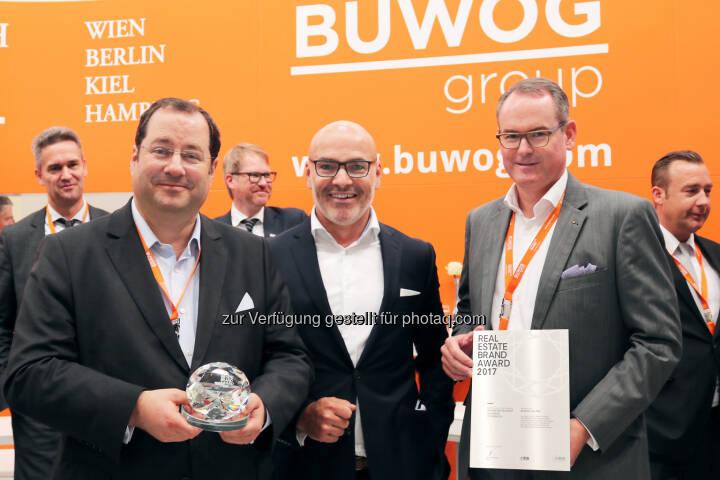 """Im Rahmen der Expo Real – der internationalen Fachmesse für Immobilien und Investitionen in München – wurden die Top-Player der Immobilienbranche ausgezeichnet. Zum dritten Mal in Folge konnte sich die Buwog Group den ersten Platz in der Kategorie """"Top 100 Residential Österreich"""" sichern. Hierbei erreichte die Marke im diesjährigen Ranking mit einem Brandvalue von 86,48 Prozent den Bestwert aller untersuchten Unternehmen. Buwog-CEO Daniel Riedl (links) und Buwog-COO Herwig Teufelsdorfer (rechts) gemeinsam mit Harald Steiner, Herausgeber des Real Estate Brand Books; Fotocredit: Buwog"""