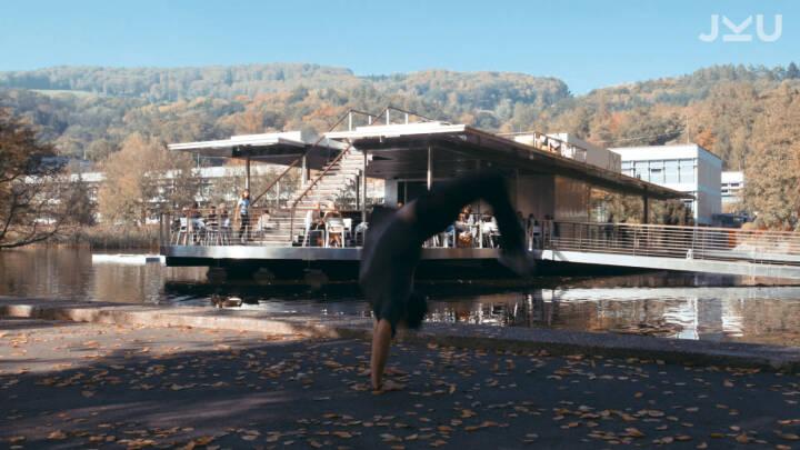 """Ein neues Video zeigt den Campus der Johannes Kepler Universität aus einer anderen, waghalsigen Perspektive und verwandelt ihn in ein Parkour-Paradies: Alex Schauer, 22-jähriges Aushängeschild der Trendsportart, die auch als """"Kunst der effizienten Fortbewegung"""" bezeichnet wird, bahnt sich seinen speziellen Weg über das JKU-Gelände. Copyright Screenshots: JKU"""